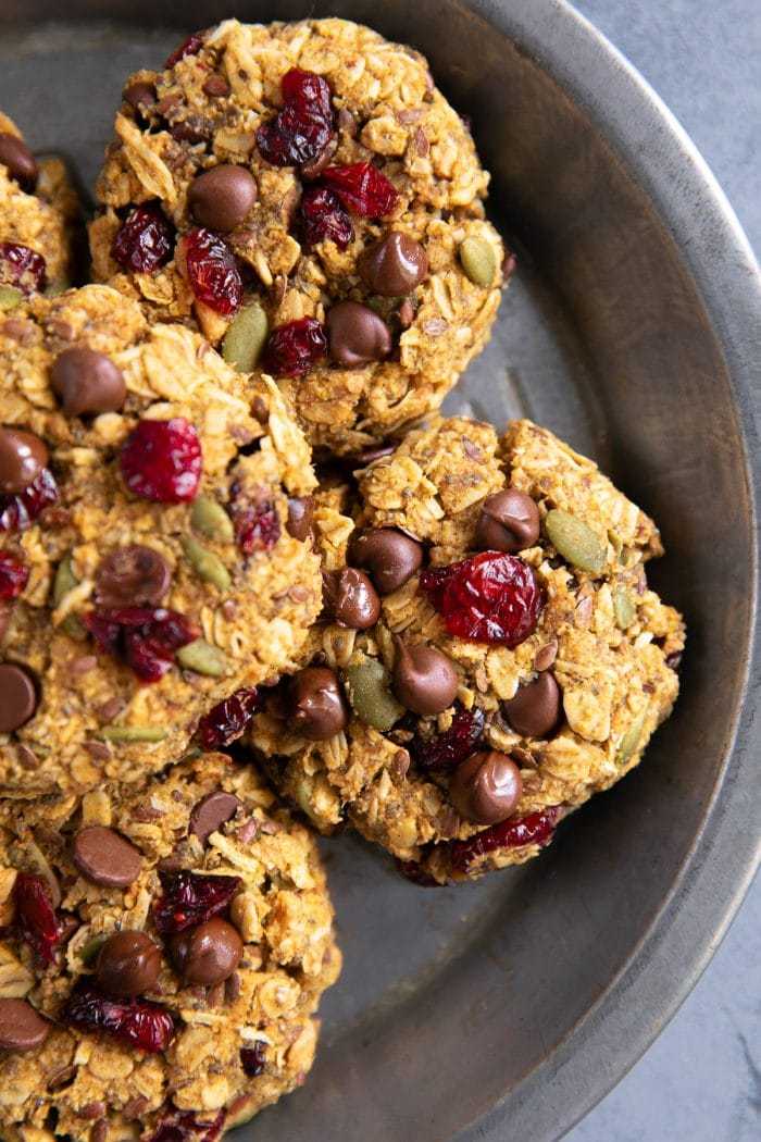 Freshly baked breakfast cookies cookies made with granola, almond flour rolled oats, maple syrup, chocolate chips, flax seeds, chia seeds, pumpkin, dried cranberries, and pumpkin seeds.