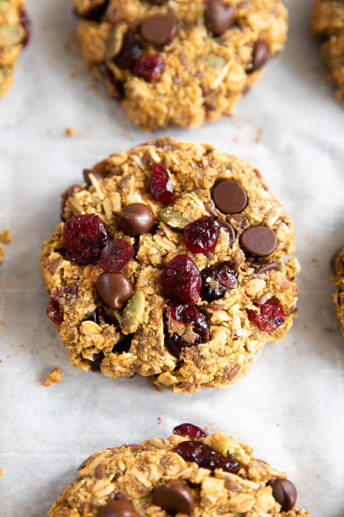Cookies made with granola, almond flour rolled oats, maple syrup, chocolate chips, flax seeds, chia seeds, pumpkin, dried cranberries, and pumpkin seeds.