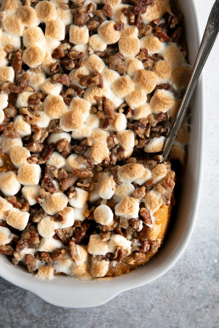Cooked sweet potato casserole topped with chopped pecans and marshmallows