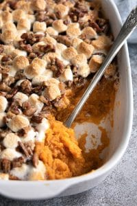 Large white casserole dish filled with sweet sweet potato casserole.