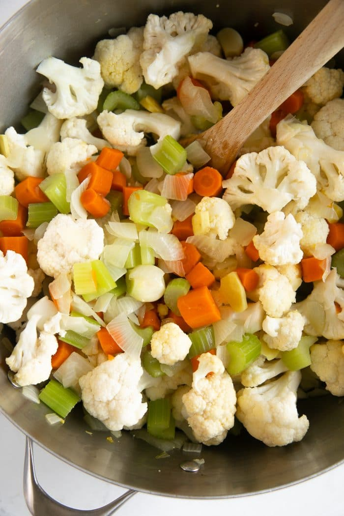 Cooking mirepoix and cauliflower florets in a large dutch oven.