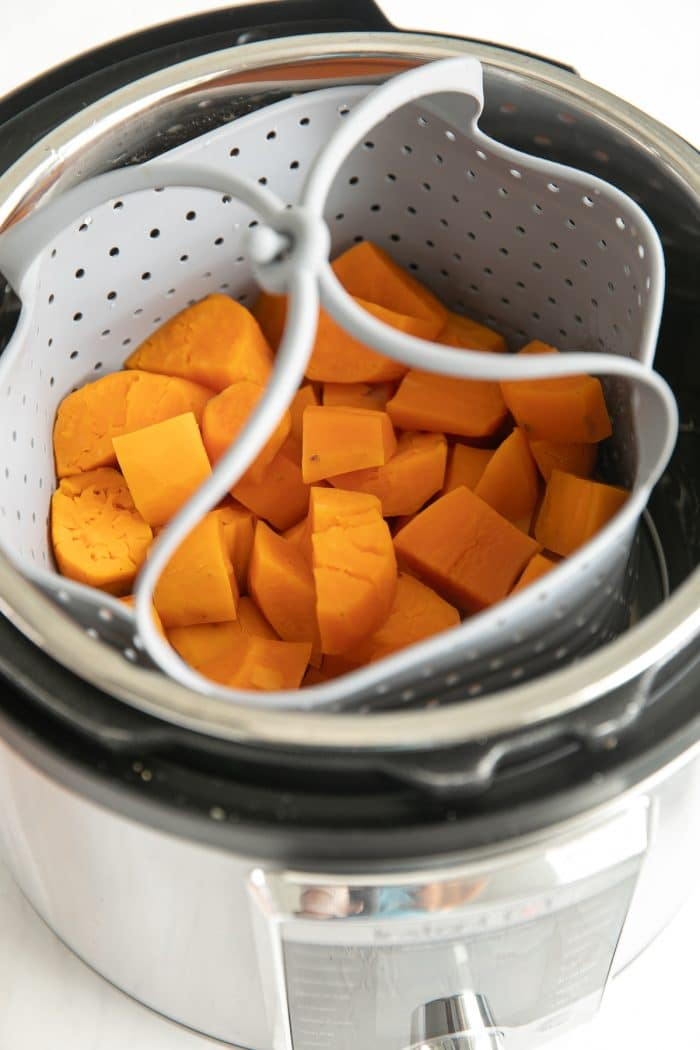 Peeled and chopped sweet potatoes in an Instant Pot steamer steamer basket.