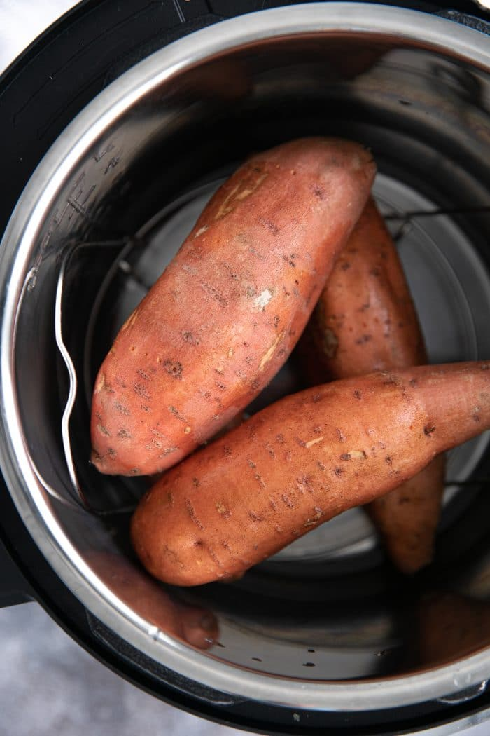 Four sweet potatoes in an Instant Pot before cooking.
