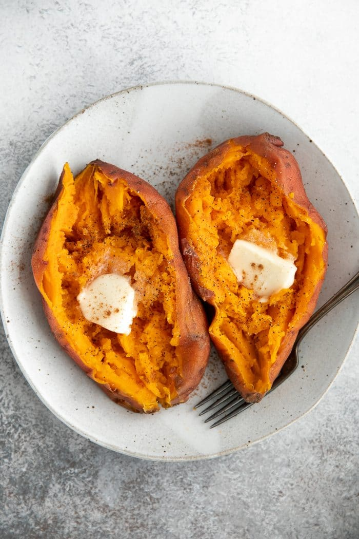 Two cooked sweet potatoes topped with butter.