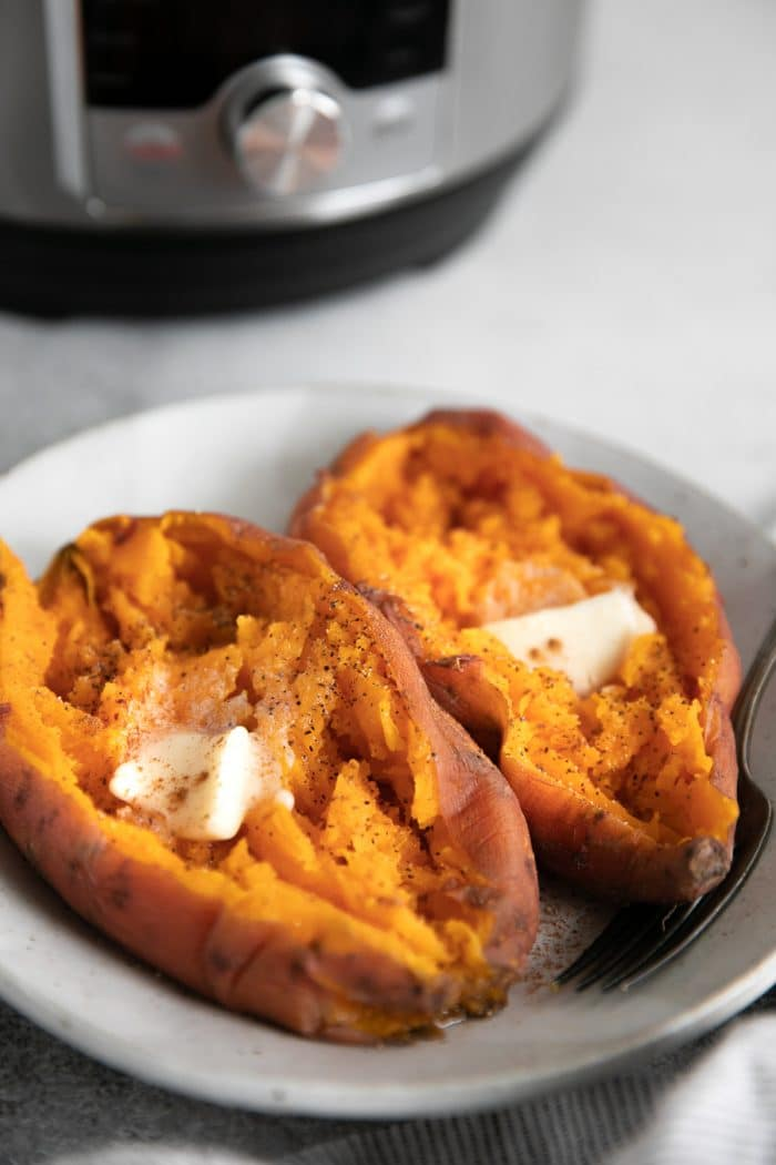 Two Instant Pot sweet potatoes cooked and split open and topped with butter.