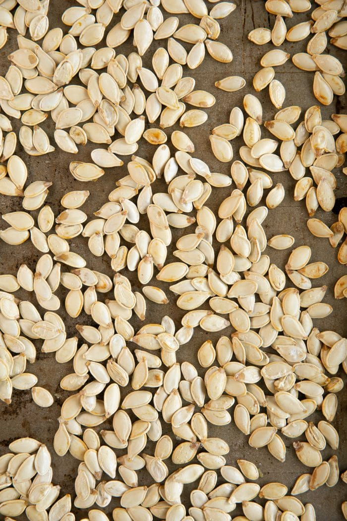 Large baking sheet filled with roasted pumpkin seeds.