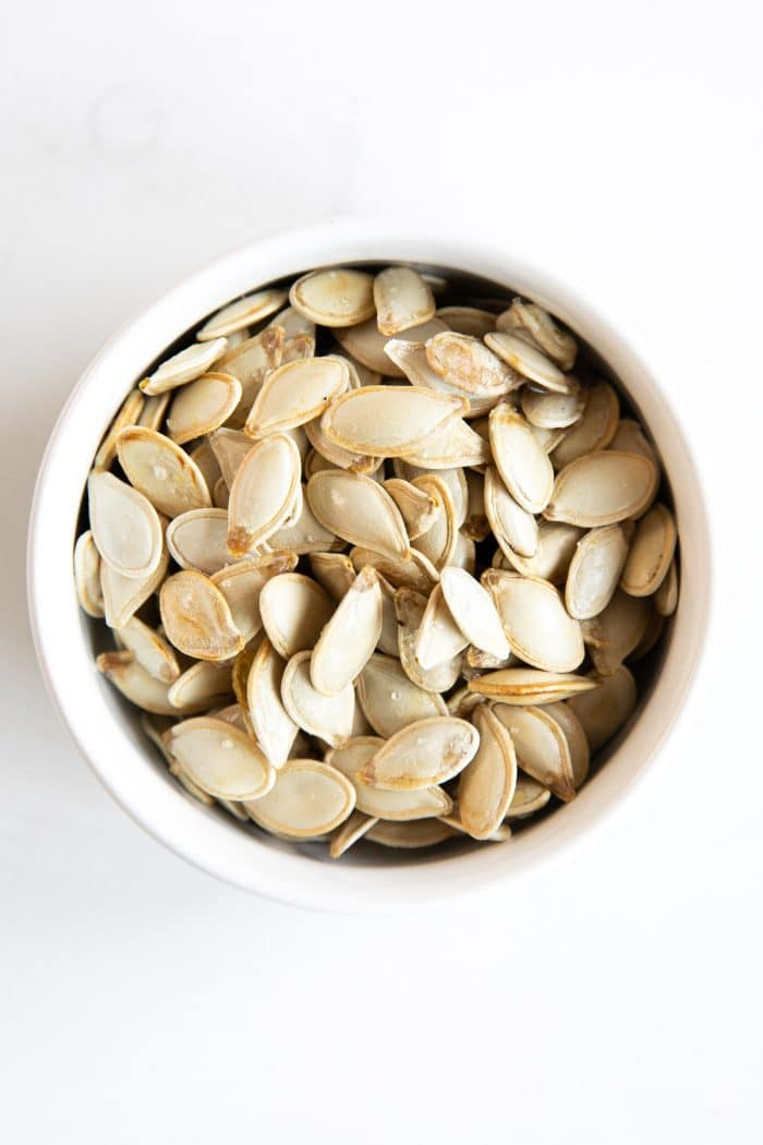 Small white bowl filled with homemade roasted pumpkin seeds