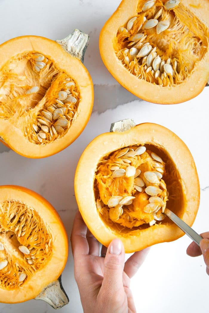 Scooping out the seeds and the guts from halved sugar pumpkins.