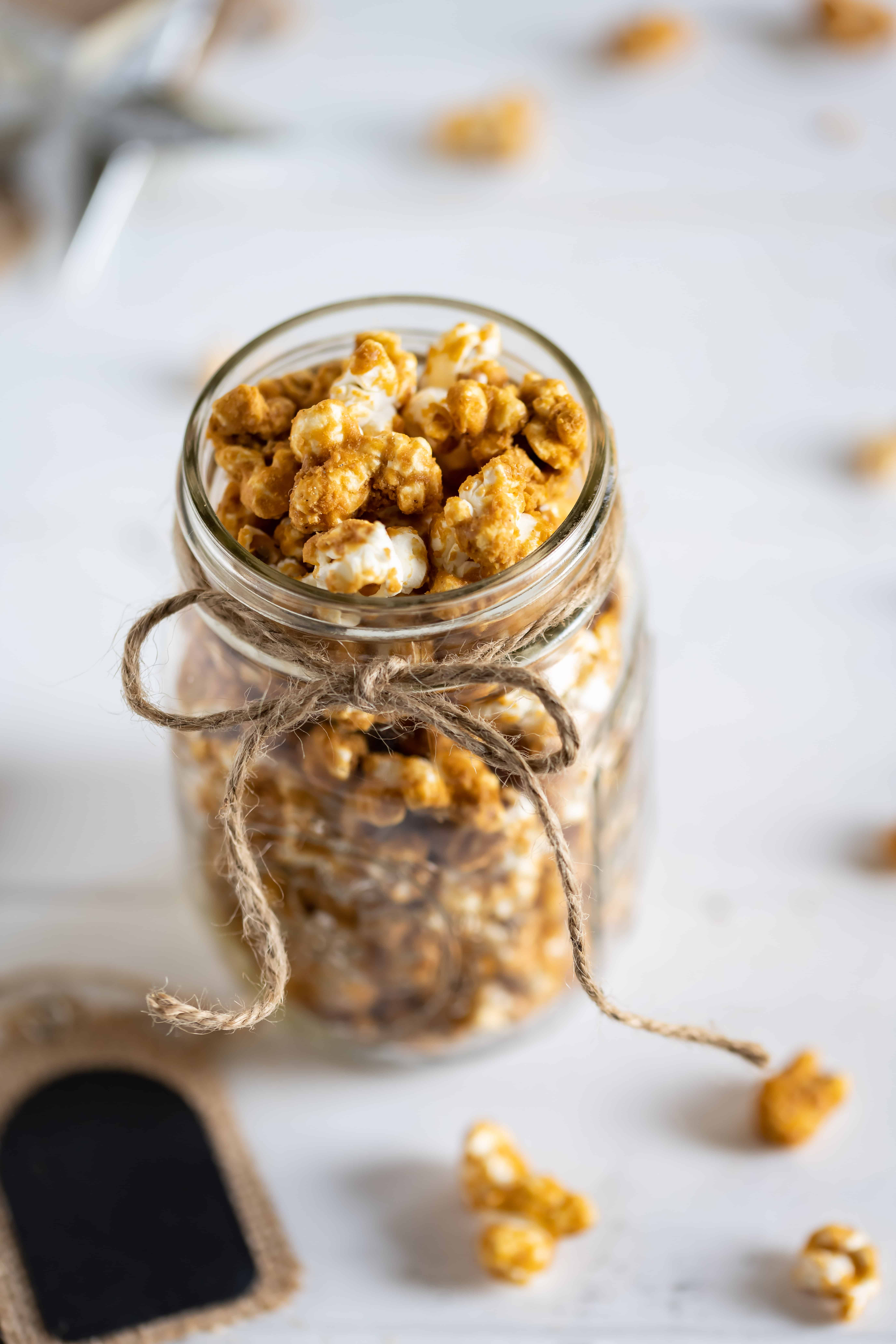 Gingerbread caramel corn in a glass mason jar wrapped with twine.