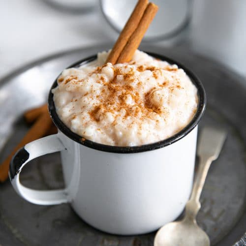 Small mug filled with arroz con leche and garnished with ground cinnamon.