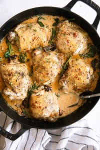 Overhead image of a large skillet filled with 6 cooked chicken thighs in a creamy tuscan sauce with sundried tomatoes and spinach.