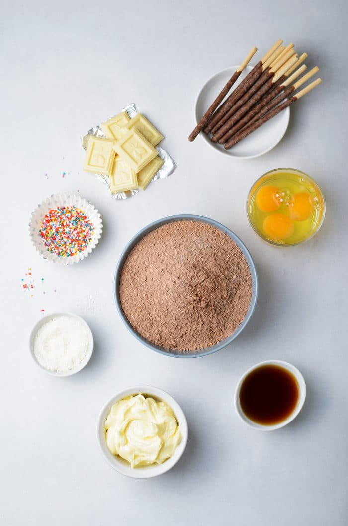 Ingredients to make chocolate cupcakes with buttercream frosting and chocolate christmas tree toppers.