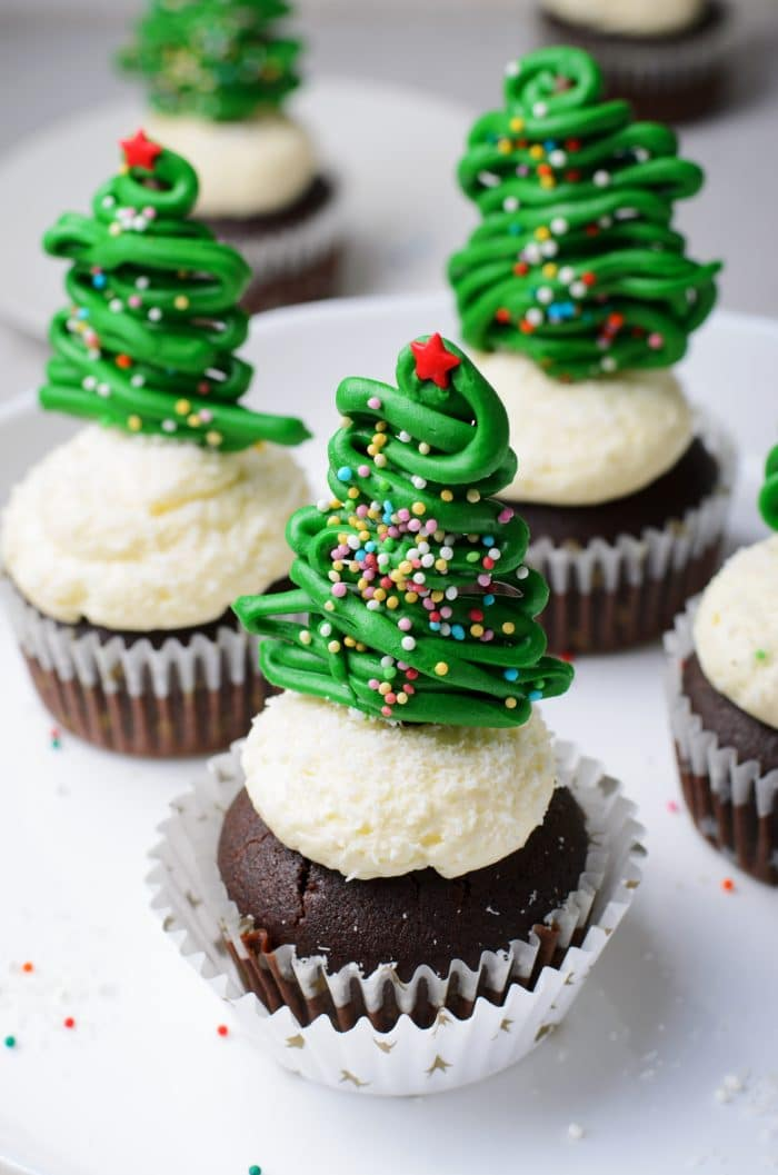 Cake stand filled with four Chocolate cupcakes with vanilla buttercream frosting and topped with a chocolate christmas tree topper.