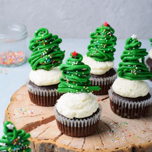 Chocolate cupcakes with vanilla buttercream frosting and topped with a chocolate christmas tree topper.