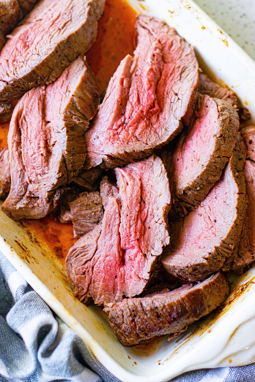 Juicy slices of roast beef tenderloin in a white baking dish