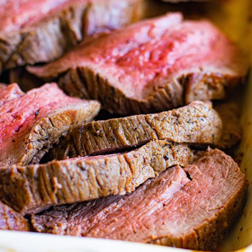 Baking dish filled with juicy sliced roast beef tenderloin