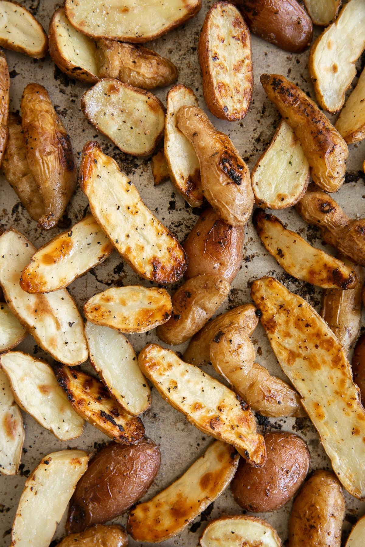 Roasted fingerling potatoes on a large baking sheet.