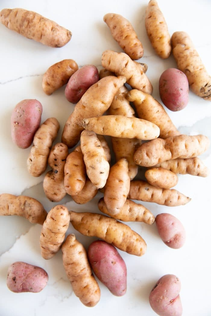 Mix of yellow and red raw fingerling potatoes.
