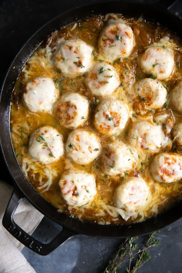 Large skillet filled with turkey meatballs simmering in a rich gravy filled with onions and covered with cheese.