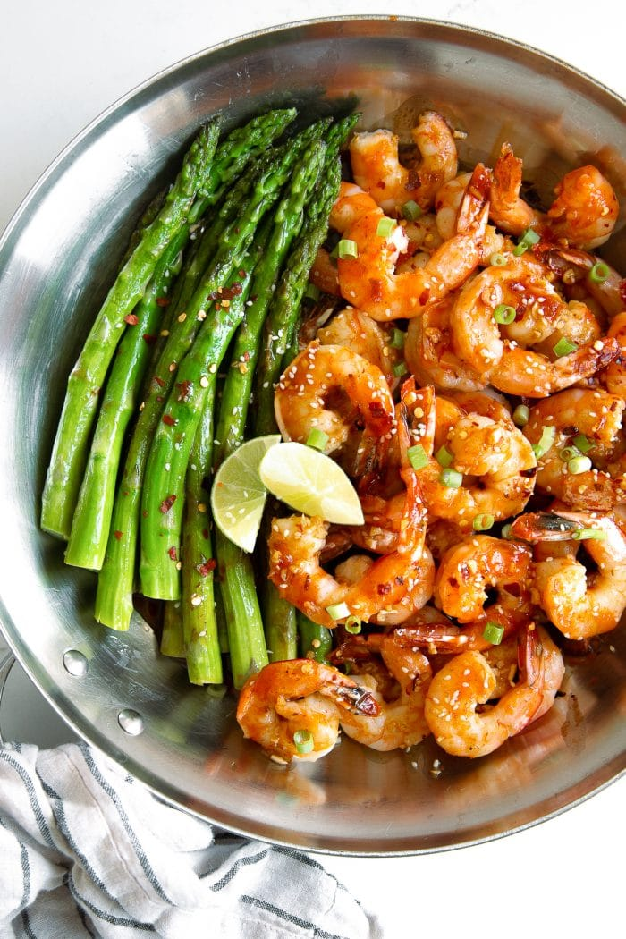 Skillet filled with jumbo tail-on cooked shrimp covered in homemade honey Sriracha sauce and served with asparagus spears.