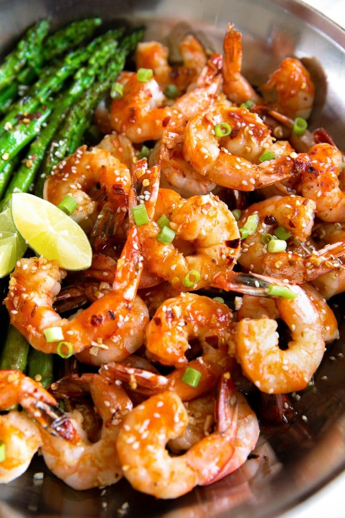 Juicy large shrimp simmered in a homemade sauce made with soy sauce, Sriracha, honey, and rice wine vinegar, and garnished with green onions and sesame seeds.