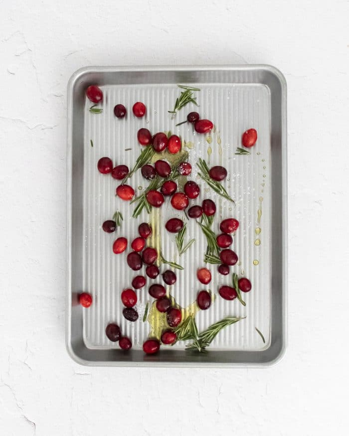 Fresh cranberries, roasemary, salt, and olive oil mixed together on a baking sheet before being roasted.