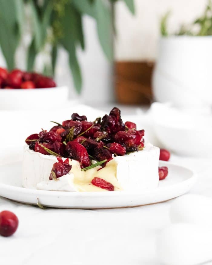 Warm baked brie topped with roasted cranberries cut open to reveal gooey, delicious cheese pouring out.