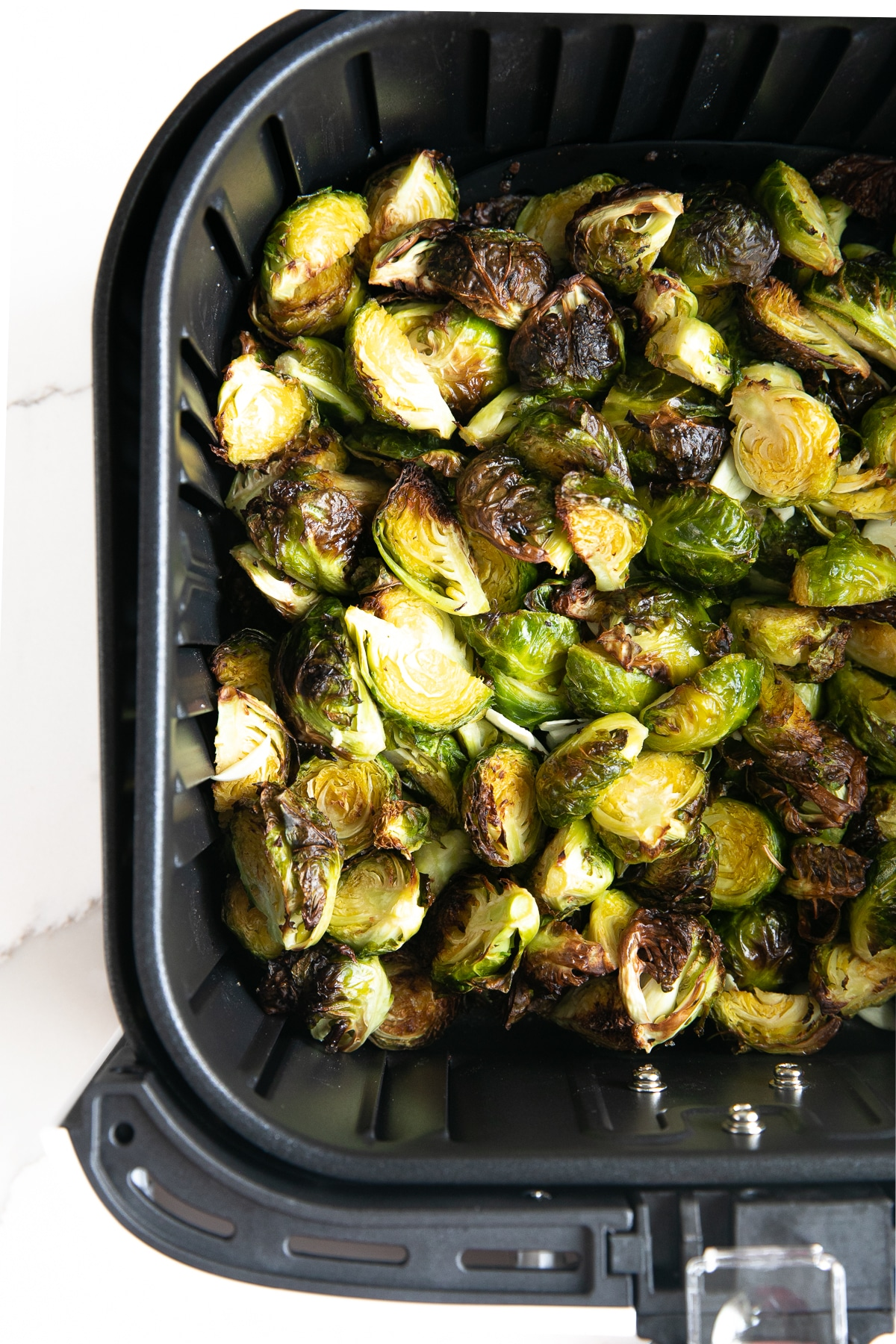 Image of fully cooked and crispy Brussels sprouts resting in the air fryer basket.