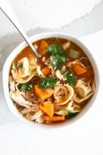White soup bowl filled with easy chicken tortellini soup made with a light tomato based broth, cheese tortellini, spinach, carrots, chicken, and garnished with red chili flakes.