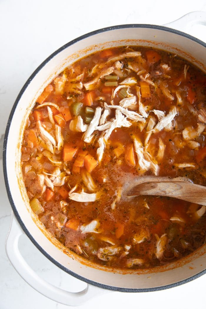 Large white Dutch oven filled with simmering tomato-based chicken broth, carrots, celery, onion, and shredded chicken.