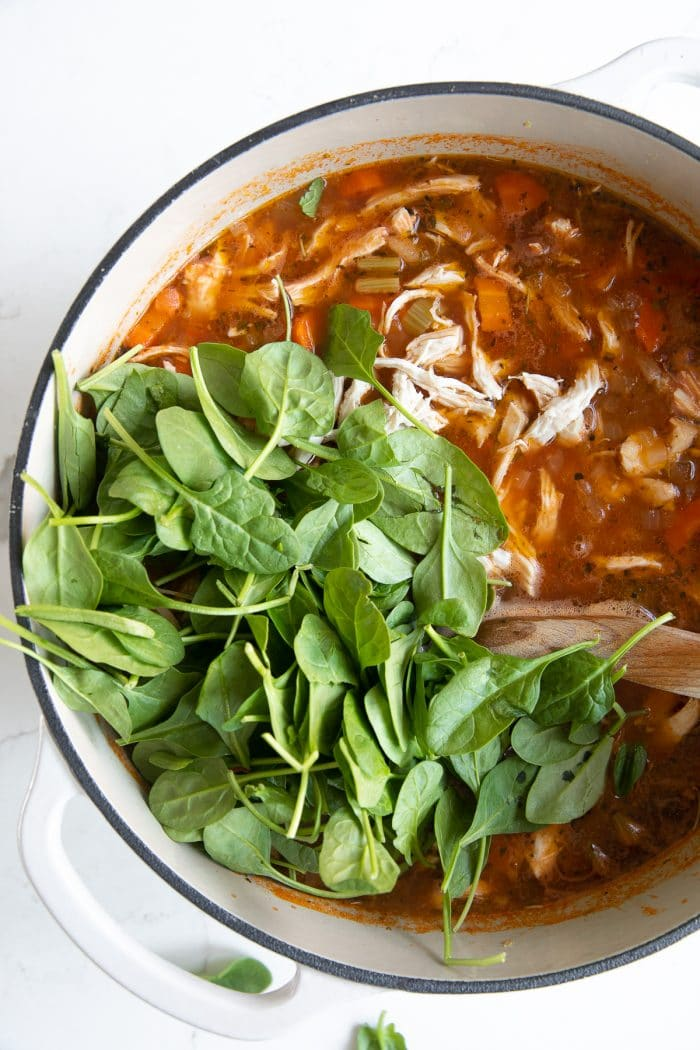 Overhead image of a large white Dutch oven filled with simmering tomato-based chicken broth, carrots, celery, onion, shredded chicken topped with several cups of fresh baby spinach..