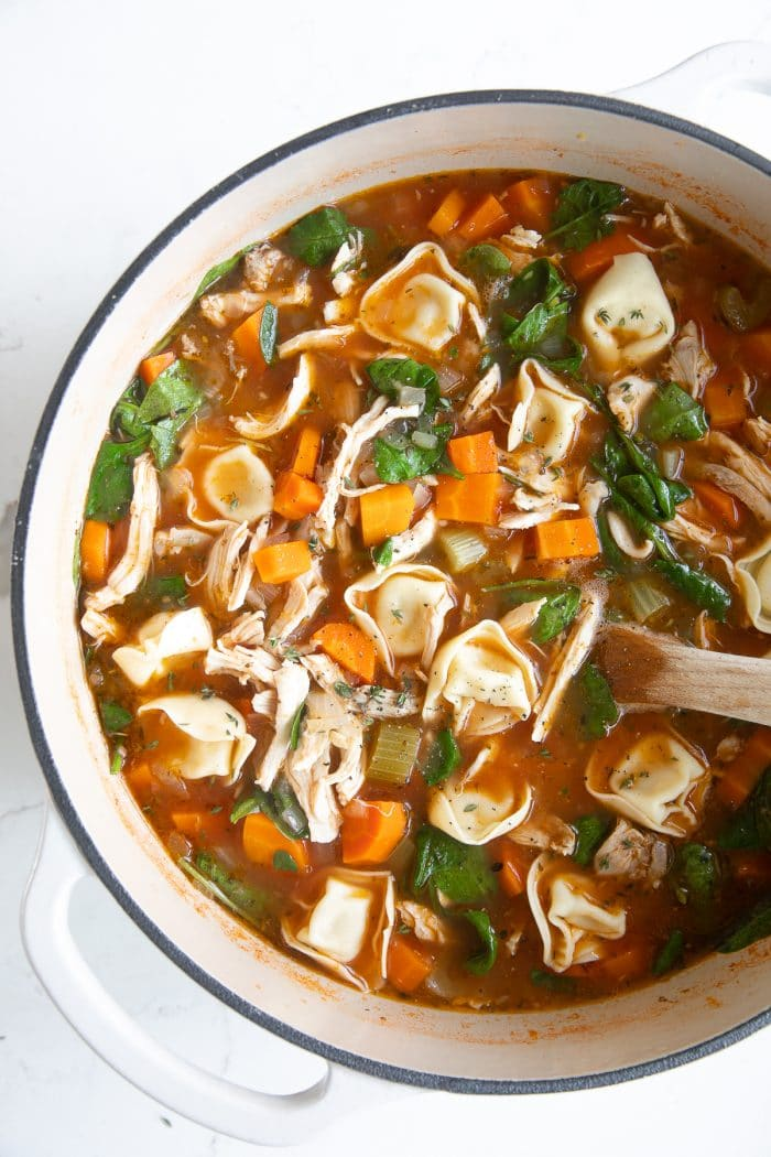 Overhead image of a large white Dutch oven filled with simmering tomato-based chicken broth, carrots, celery, onion, shredded chicken, spinach, and four-cheese tortellini.