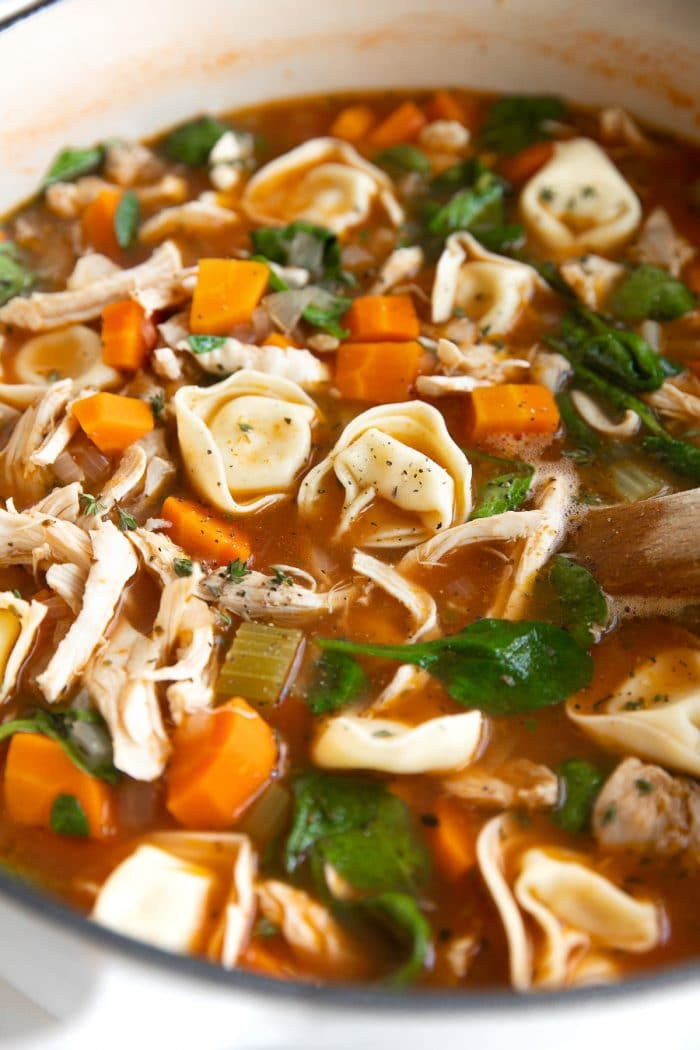 Close up image of a large white Dutch oven filled with simmering tomato-based chicken broth, carrots, celery, onion, shredded chicken, spinach, and four-cheese tortellini.