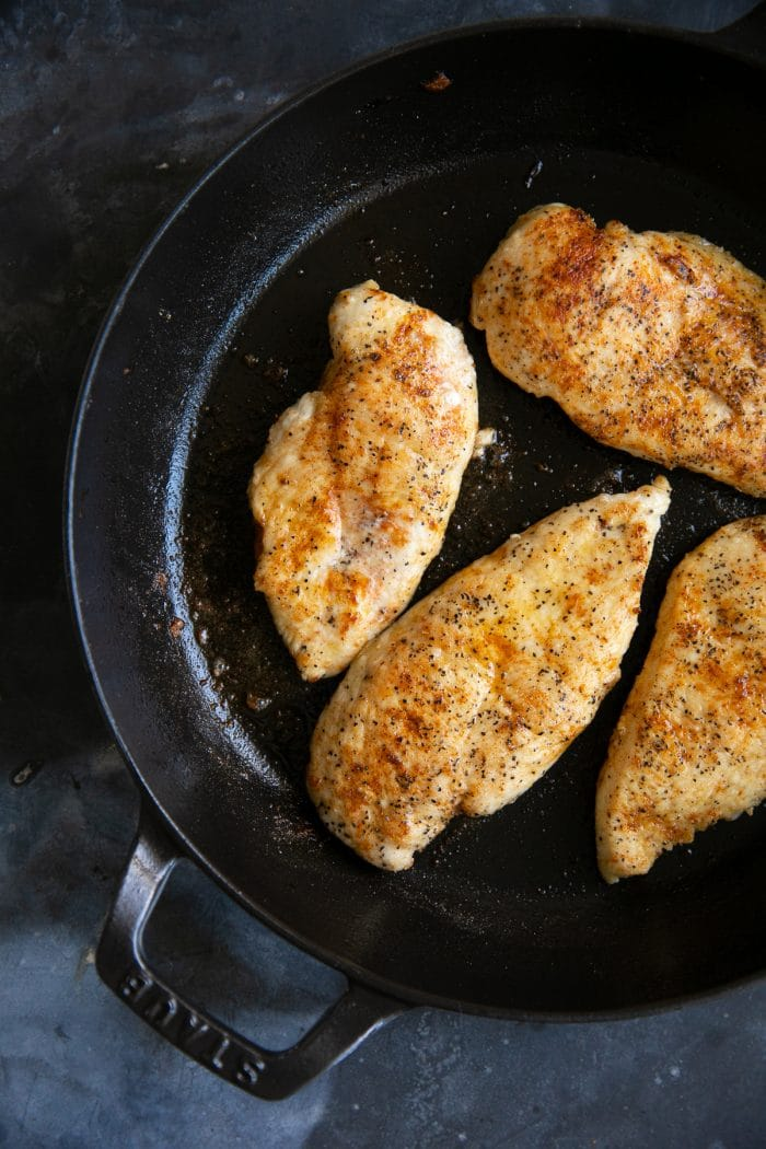 Cooked chicken cutlets resting in a large skillet.