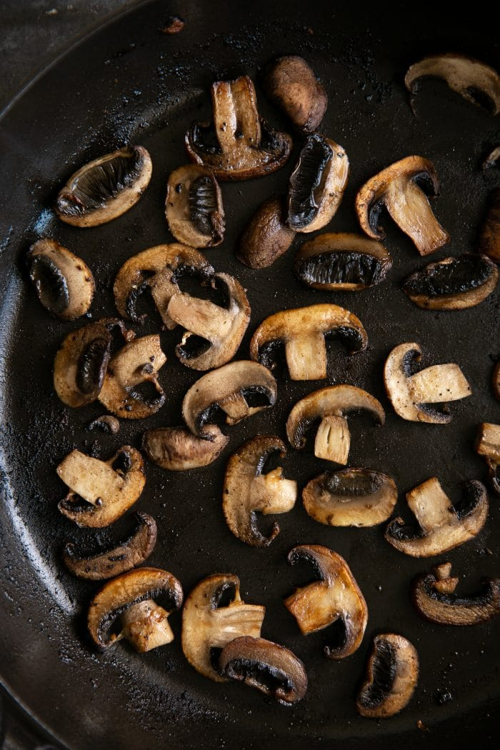 Sauteed mushrooms in a large heavy-bottomed skillet.