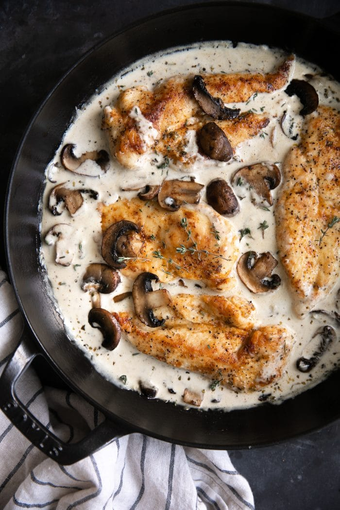 Large heavy-bottomed skillet filled with cooked chicken cutlets simmering in a homemade mushroom cream sauce.