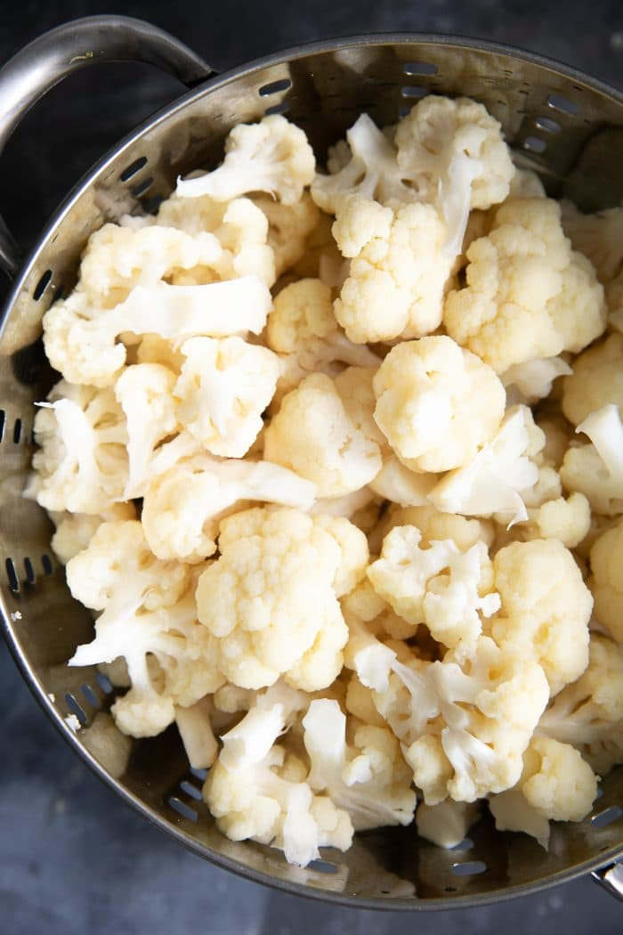 Blanched cauliflower in a large colander.