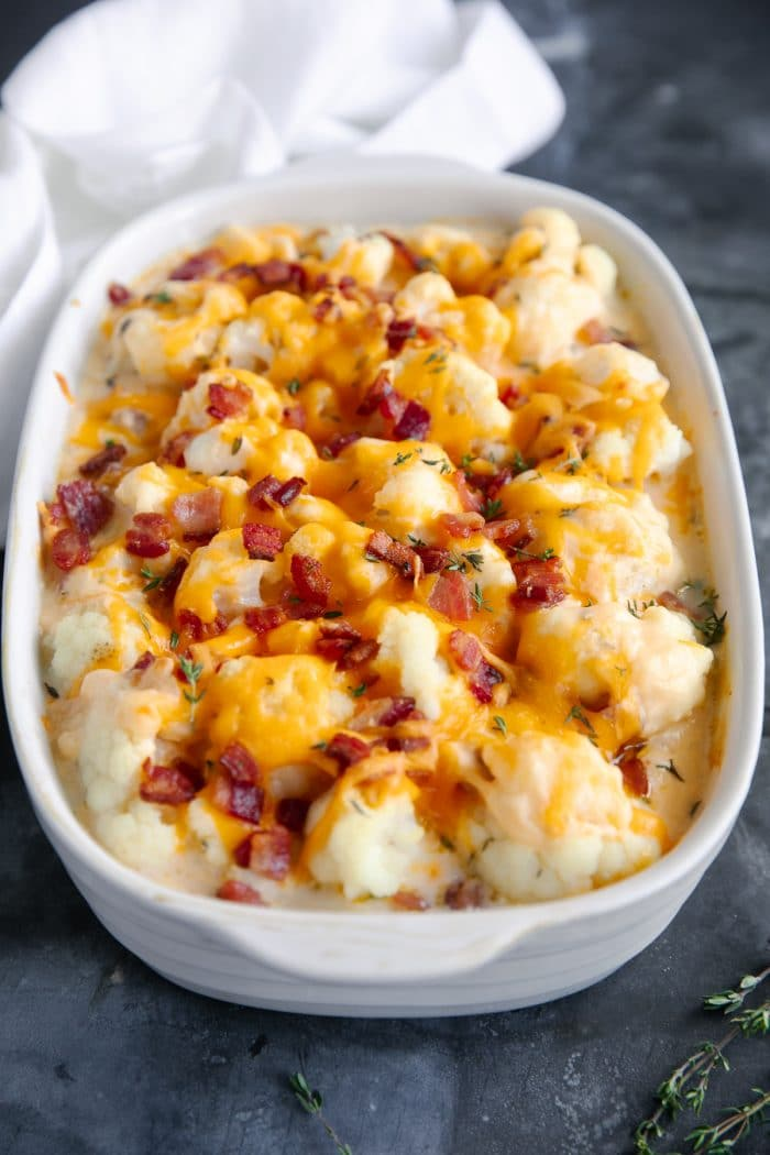 White casserole dish filled with cauliflower and cheese sauce and topped with melted cheese and bacon bits.