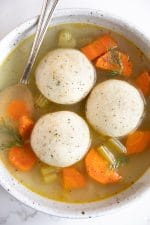 Shallow soup bowl filled with three matzo balls in a vegetable soup.