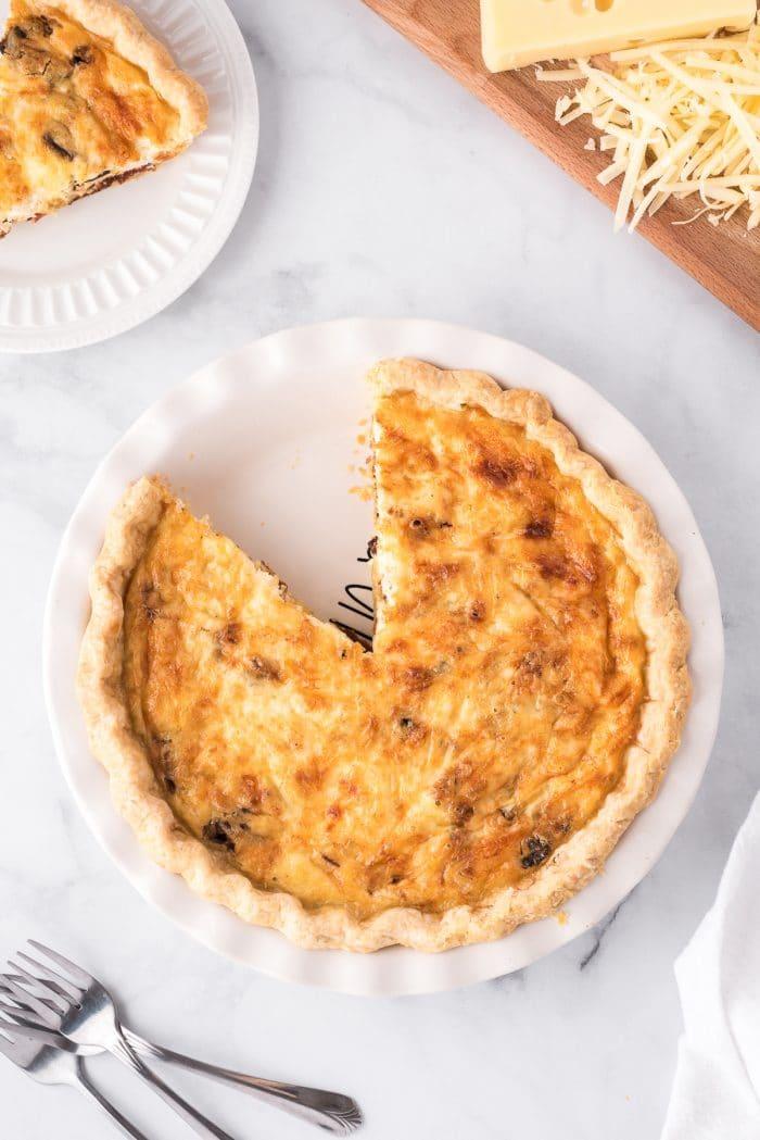 Quiche lorraine in a white pie dish.