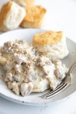 White plate with a fluffy buttermilk biscuit topped with creamy sausage gravy.
