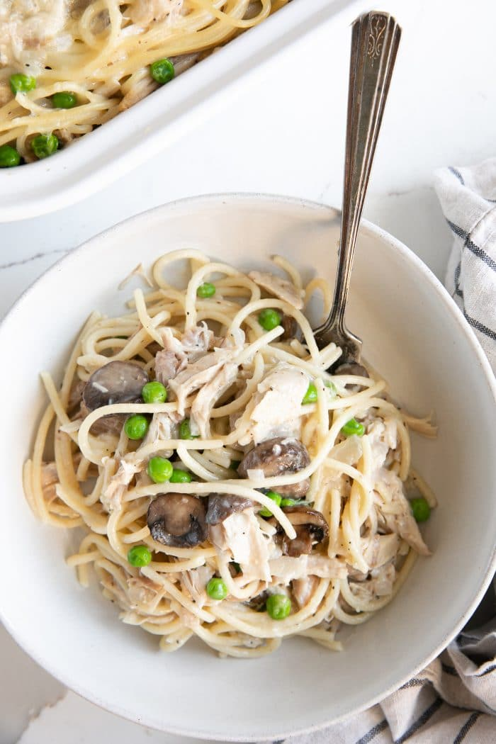 White bowl filled with creamy turkey tetrazzini with peas, mushrooms, and chunks of turkey.