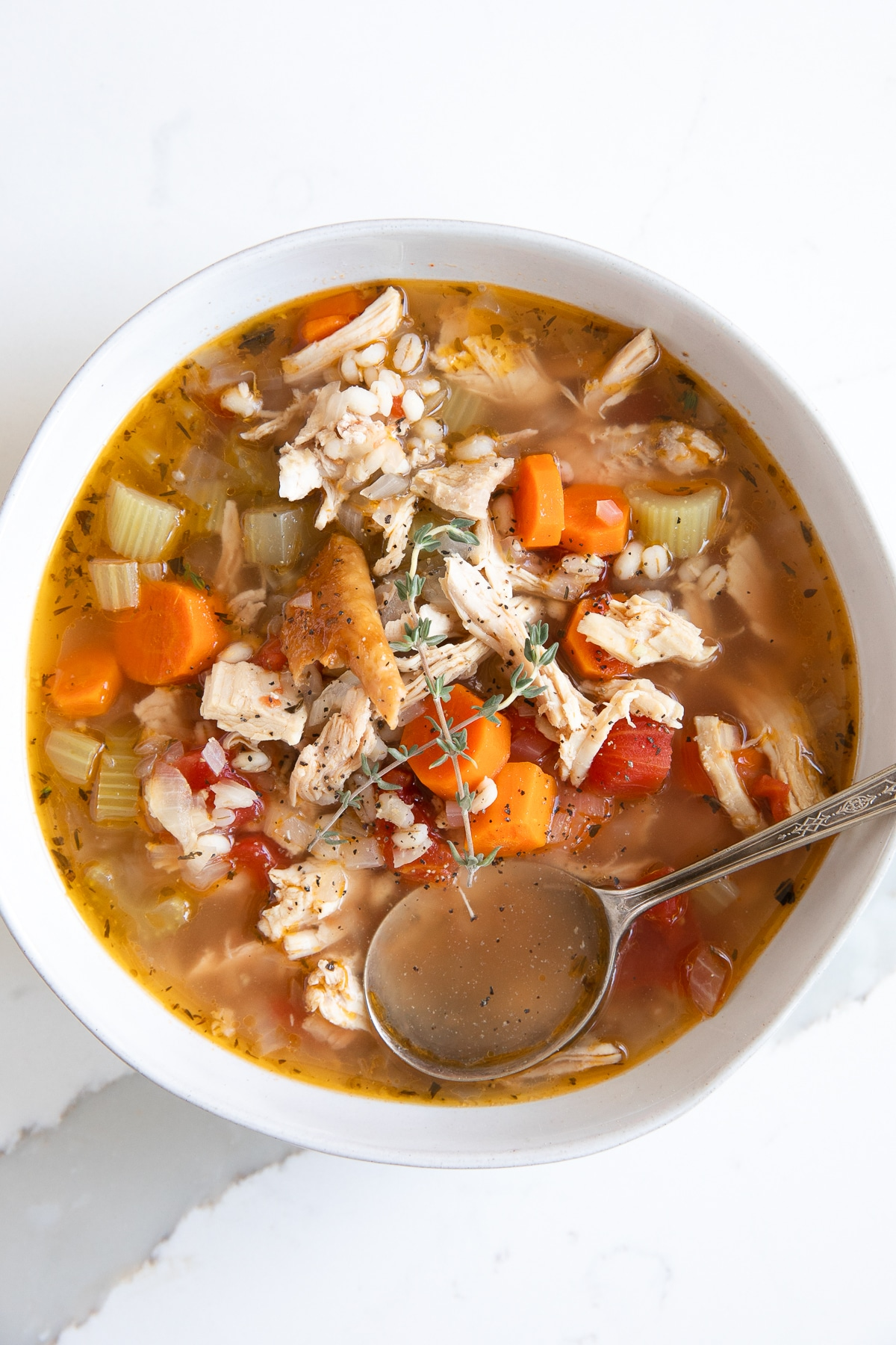 White shallow soup bowl filled with easy turkey soup filled with veggies, tomatoes, turkey, and barley.