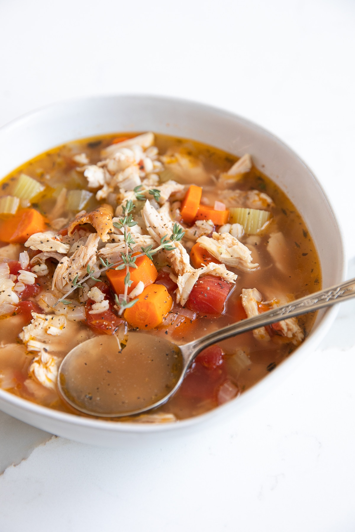 White shallow soup bowl filled with homemade leftover turkey soup filled with veggies, tomatoes, turkey, and barley.
