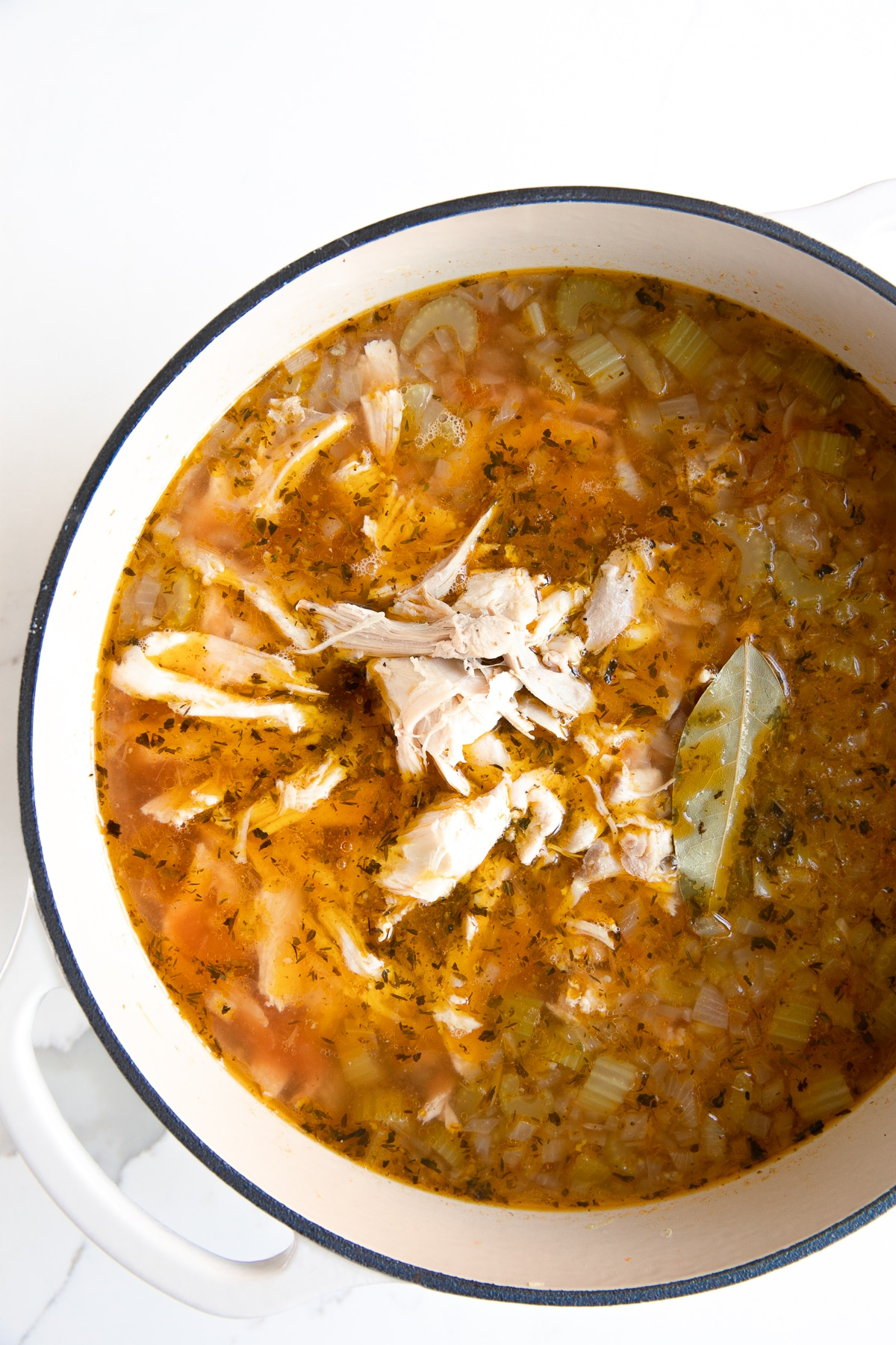 Large Dutch oven filled with simmering hot turkey soup with veggies and barley.