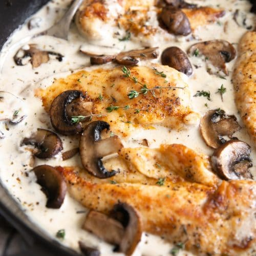 mushroom cream sauce and seared chicken breasts in a large skillet
