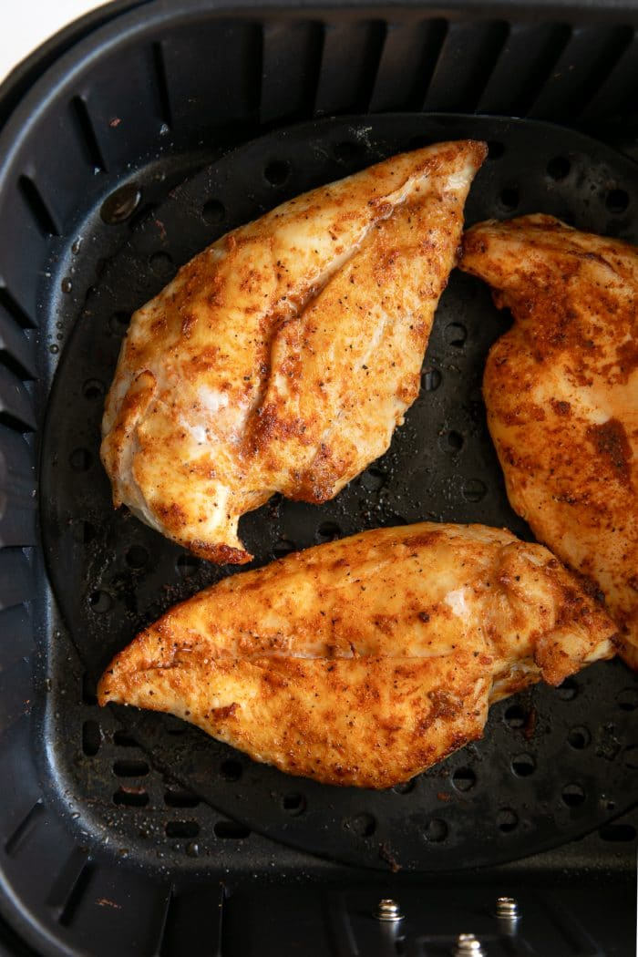 Image of three well-seasoned whole chicken breasts in a large air fryer just after cooking.