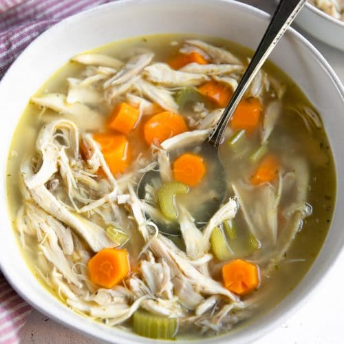 Chicken soup in a white bowl with carrots celery and onions