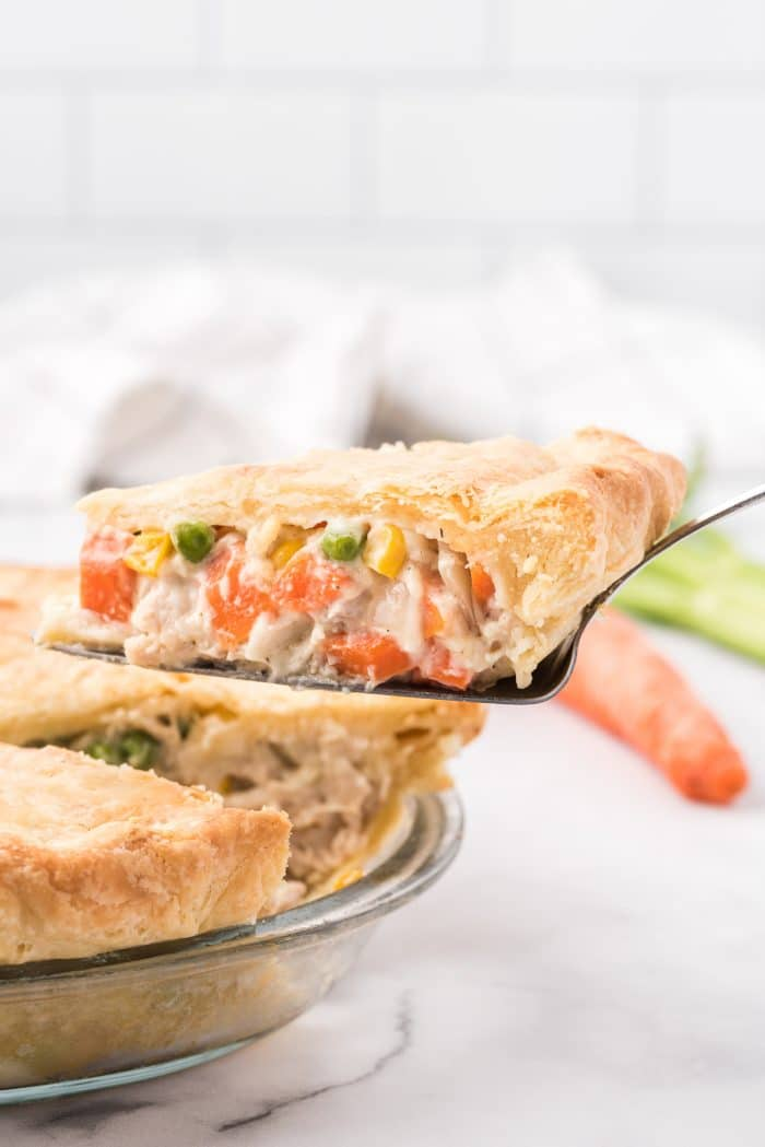 Image of a a single slice of chicken pot pie being removed from the whole pie.