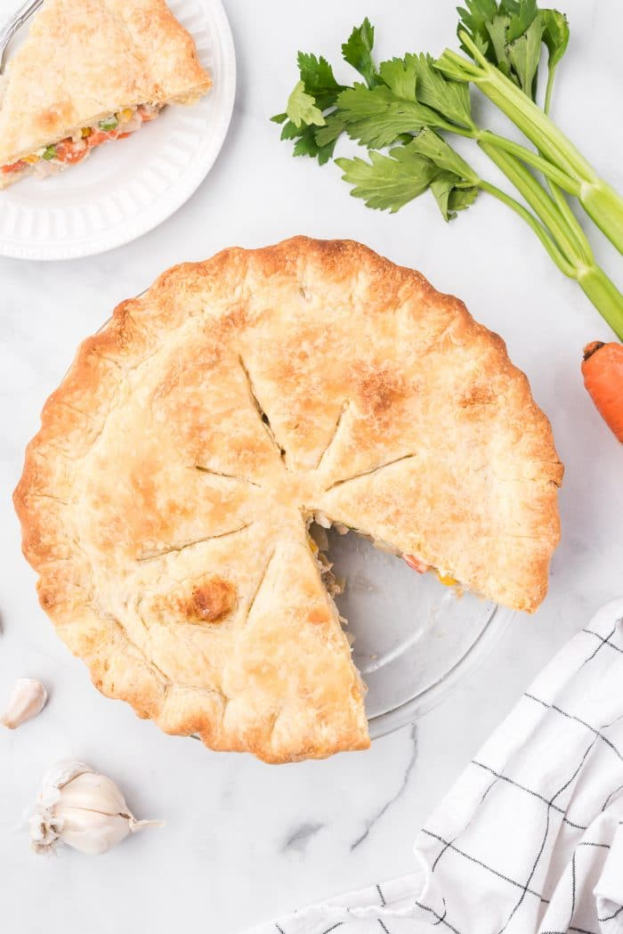Overhead image of a chicken pot pie in a pie dish with one single sliced removed.